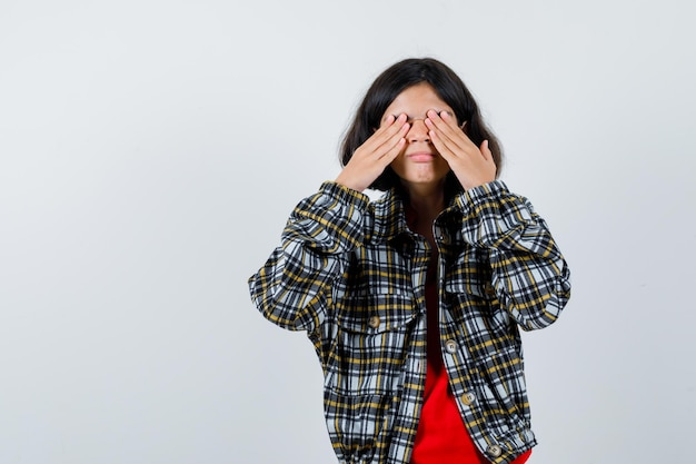 チェックのシャツと赤いtシャツを着た少女が手で目を覆い、真面目な正面図を見てください。