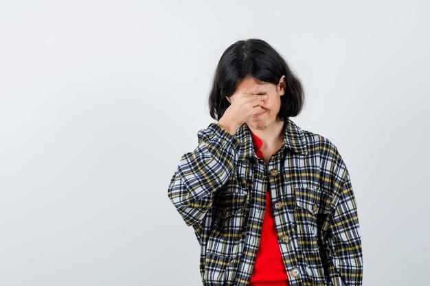 チェックシャツと赤いtシャツの少女が手で顔を覆い、真剣に見える、正面図。