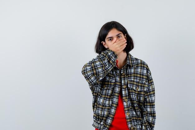 Молодая девушка в клетчатой рубашке и красной футболке закрывает рот рукой и выглядит удивленным, вид спереди.