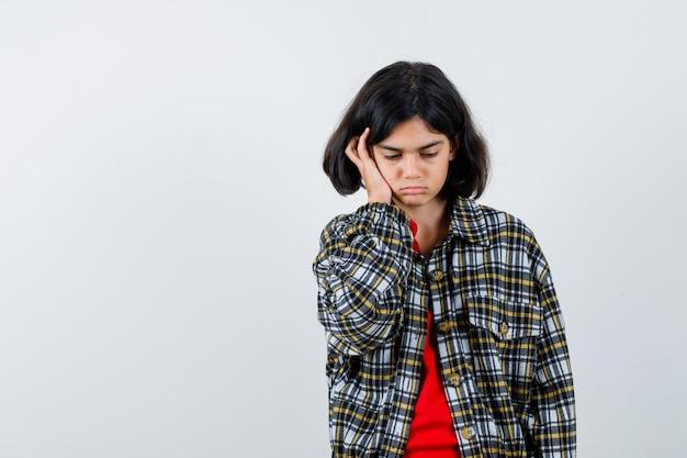 チェックシャツと赤いtシャツの若い女の子が手のひらに頬を傾けて真剣に見える、正面図。