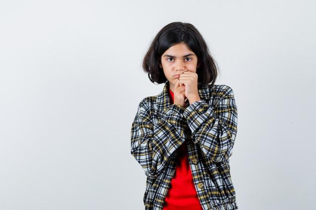 Молодая девушка в клетчатой рубашке и красной футболке, опираясь подбородком на руки и серьезным взглядом, вид спереди.