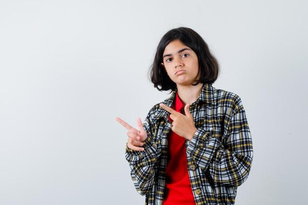 人差し指で左を指して真剣に見えるチェックシャツと赤いtシャツの少女、正面図。