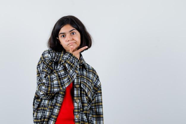 체크 셔츠와 빨간 티셔츠를 입은 어린 소녀가 검지 손가락으로 오른쪽을 가리키고 진지한 앞모습을 보고 있습니다.