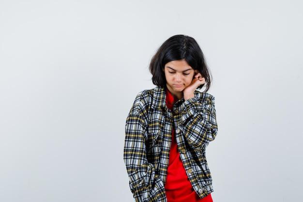 Молодая девушка в клетчатой рубашке и красной футболке, положив руку на ухо, смотрит вниз и выглядит счастливой, вид спереди.