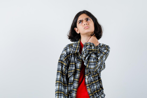 チェックのシャツと赤いtシャツを着た少女が首に手を置いて、上を見て、急いで、正面図。