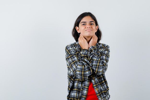 Молодая девушка в клетчатой рубашке и красной футболке кладет руки на шею и выглядит мило, вид спереди.