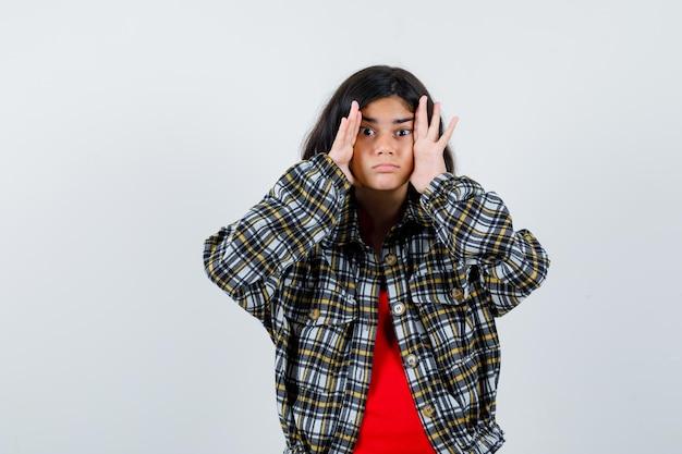 체크 셔츠와 빨간 티셔츠를 입은 어린 소녀가 얼굴에 손을 대고 귀엽고 앞모습을 보고 있습니다.