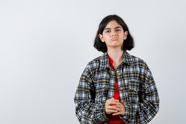 チェックシャツと赤いtシャツの若い女の子が手をこすり、真剣に見える、正面図。