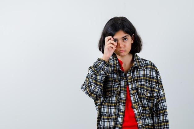 チェックシャツと赤いtシャツの若い女の子が顔を引っ掻いて真剣に見える、正面図。