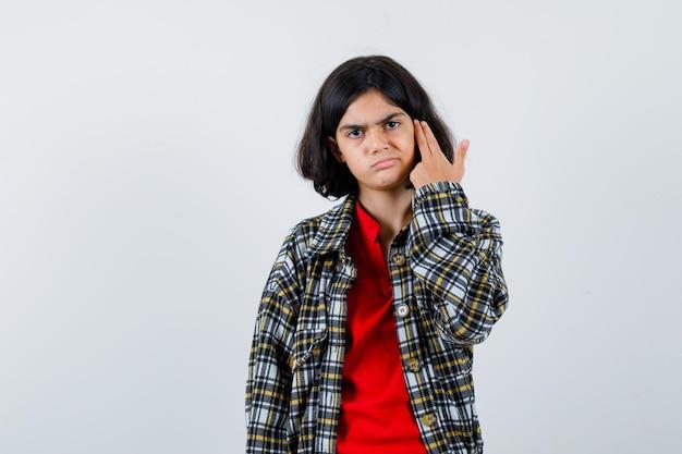 Молодая девушка в клетчатой рубашке и красной футболке показывает жест пистолета возле головы и выглядит серьезным, вид спереди.