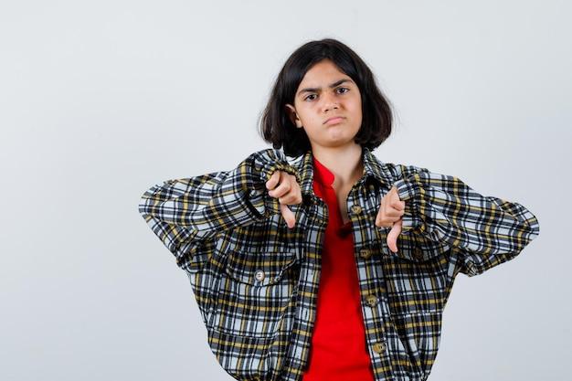 Молодая девушка в клетчатой рубашке и красной футболке показывает палец вниз обеими руками и выглядит недовольным, вид спереди.