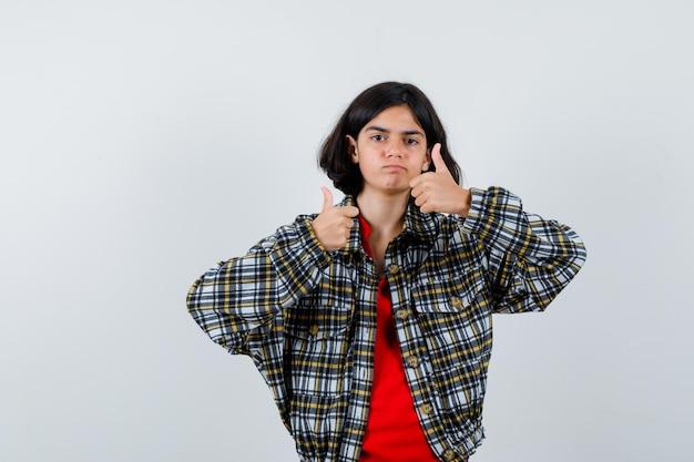 체크 셔츠와 빨간 티셔츠를 입은 어린 소녀가 두 손으로 엄지손가락을 치켜들고 귀엽게 보이는 전면 전망을 보여줍니다.