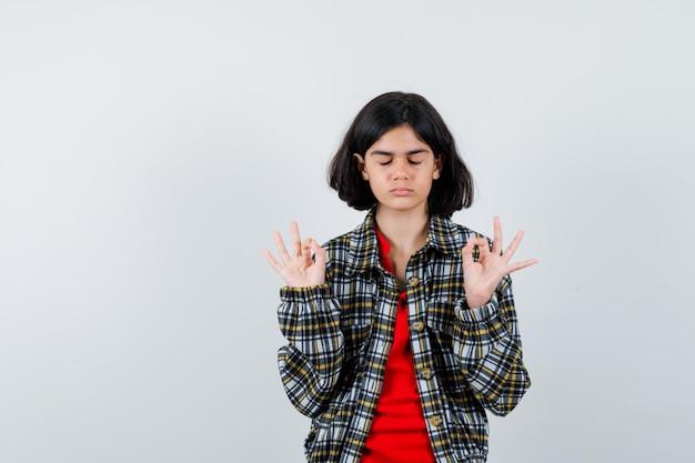 체크 셔츠와 빨간 티셔츠를 입은 어린 소녀가 명상 포즈로 서서 차분한 앞모습을 보고 있습니다.