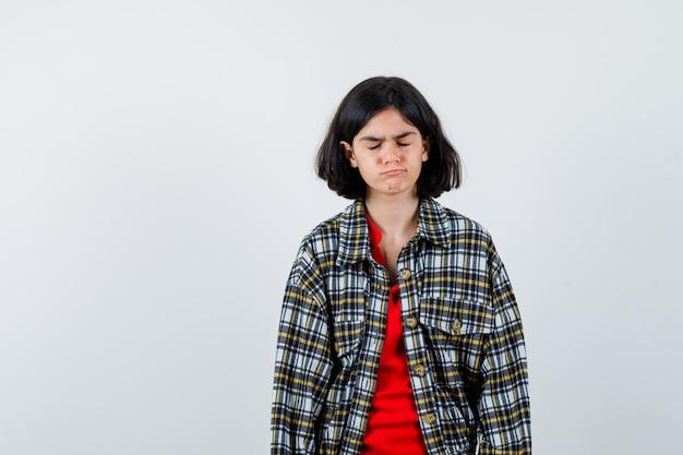 チェックのシャツと赤いtシャツを着た少女がまっすぐ立って、目を閉じてカメラに向かってポーズをとって、真面目な正面図を見てください。