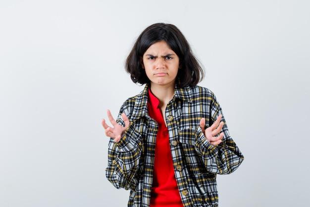 チェックのシャツと赤いtシャツを着た少女が何かを受け取り、怒っているように手を伸ばして、正面図。