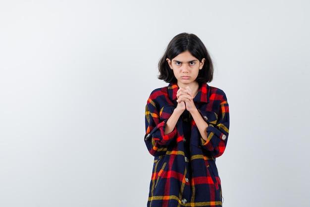 チェックシャツを着た少女は、祈りの位置で手を握りしめ、焦点を合わせて、正面図を見てください。