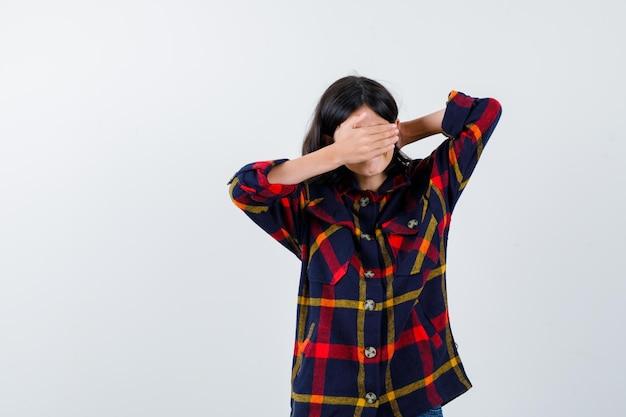 Молодая девушка в клетчатой рубашке закрывает глаза рукой, держа руку за голову и серьезная, вид спереди.
