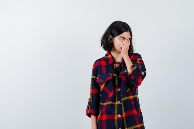 체크 셔츠를 입은 어린 소녀가 손으로 입과 코를 덮고, 멀리 바라보고 지친 모습을 보고 있습니다.