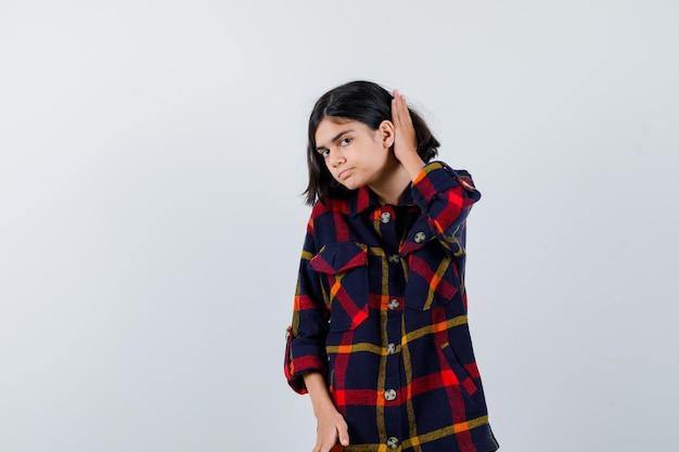 체크 셔츠를 입은 어린 소녀가 귀 근처에 손을 잡고 무언가를 듣고 집중하여 정면을 바라보고 있습니다.