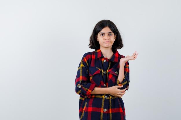 何かを持って真面目な顔をして手を伸ばしながら額に手をかざすチェックシャツの少女、正面図。