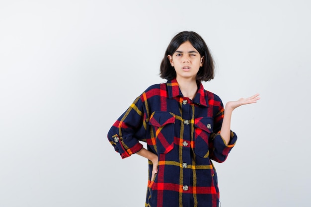 何かを持ってウインクしてキュートに見えるように手を伸ばしながら腰に手をかざすチェックシャツの少女、正面図。