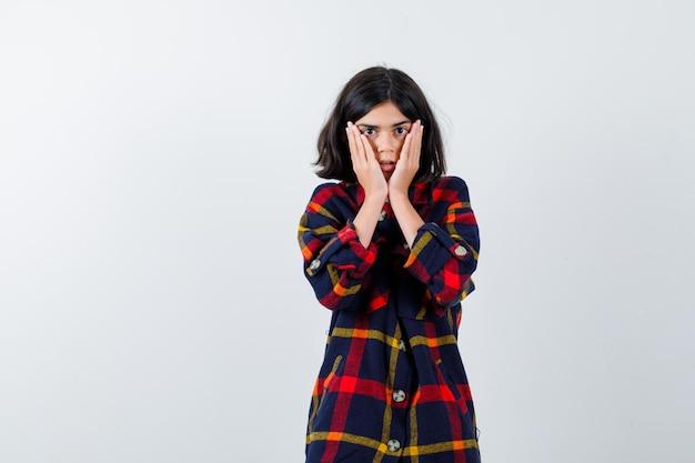 체크 셔츠를 입은 어린 소녀가 뺨에 손을 대고 겁에 질린 표정으로 정면을 바라보고 있습니다.