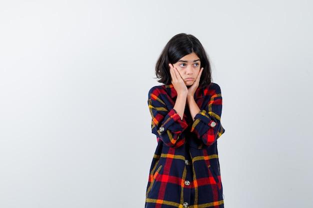 Молодая девушка в клетчатой рубашке, взявшись за руки на щеках и выглядя серьезной, вид спереди.
