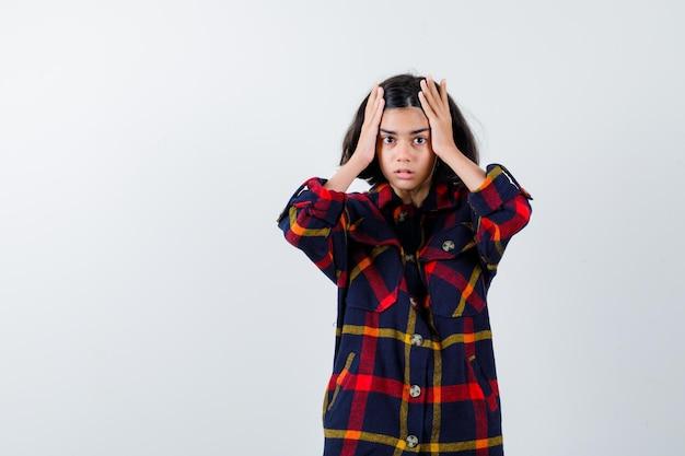 머리에 손을 잡고 불안, 전면보기 찾고 체크 셔츠에 어린 소녀.