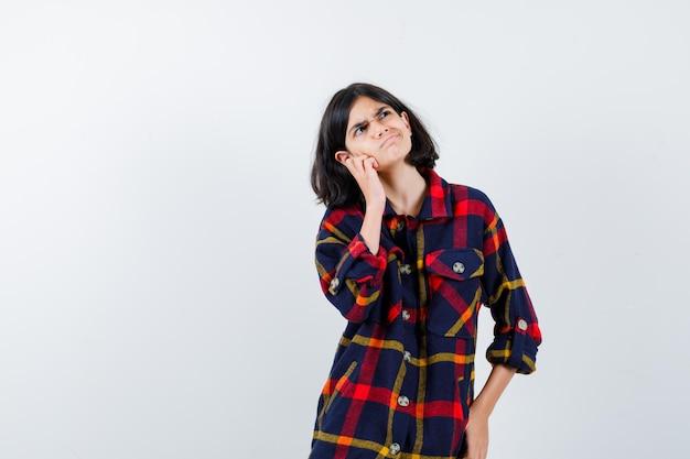 체크 셔츠를 입은 어린 소녀가 손바닥에 뺨을 기대고 무언가에 대해 생각하고 잠겨있는 앞모습을 보고 있습니다.