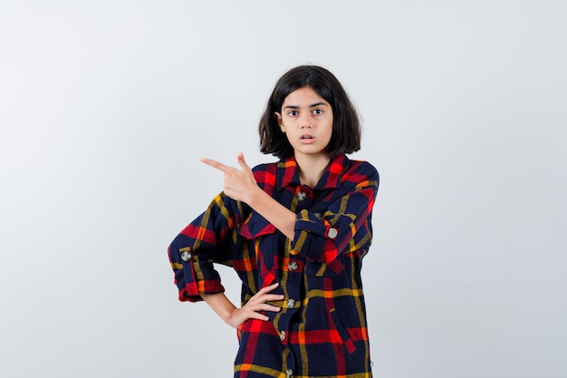 체크 셔츠를 입은 어린 소녀가 검지 손가락으로 왼쪽을 가리키며 허리에 손을 대고 진지한 정면을 바라보고 있습니다.