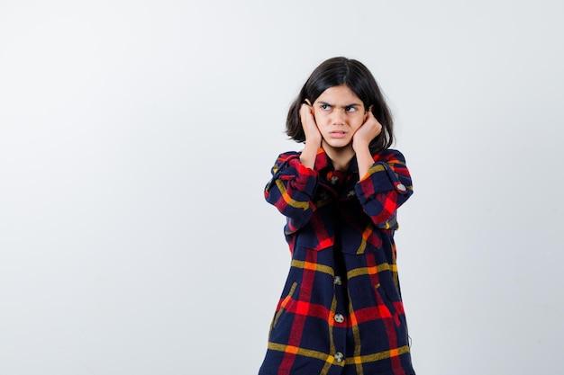 チェックシャツを着た少女が耳に手を押して、目をそらし、焦点を合わせて見ている、正面図。