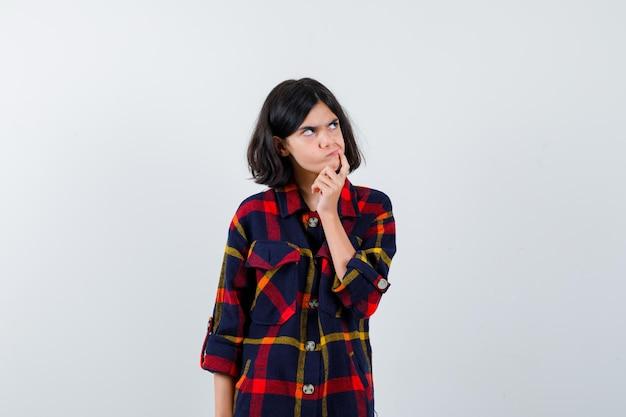 Молодая девушка в клетчатой рубашке, положив руку на подбородок, глядя вверх и задумчиво, вид спереди.