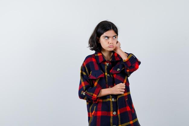 체크 셔츠를 입은 어린 소녀가 귀에 손을 대고 멀리 바라보고 진지한 전면 모습을 보고 있습니다.