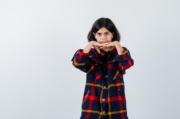 Молодая девушка в клетчатой рубашке, положив руки под подбородок и выглядя мило, вид спереди.