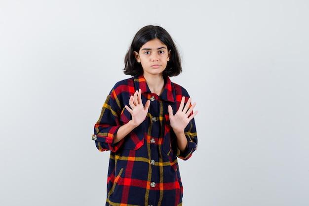 チェックシャツを着た少女が降伏ポーズで手を上げて怖がって、正面図。