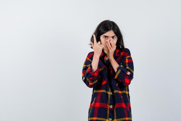 Молодая девушка в клетчатой рубашке поднимает указательный палец в жесте эврики, кладет руку на нос и выглядит серьезным, вид спереди.