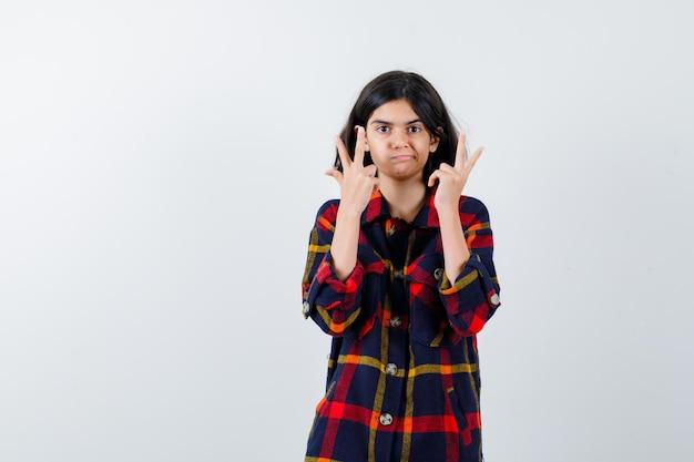 체크 셔츠를 입은 어린 소녀가 평화 제스처를 보이고 귀엽고 앞모습이 보입니다.