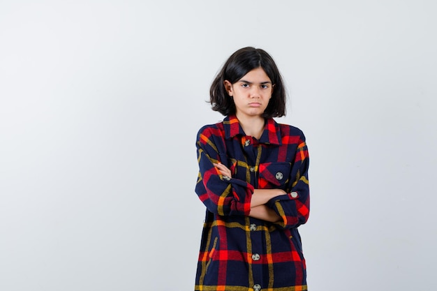 Молодая девушка в клетчатой рубашке стоя, скрещенными руками и серьезным взглядом, вид спереди.