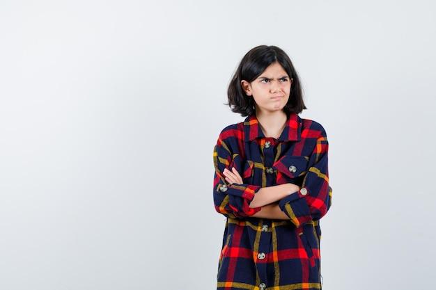 チェックシャツを着た少女が腕を組んで、目をそらし、急いでいる様子を正面から見た。