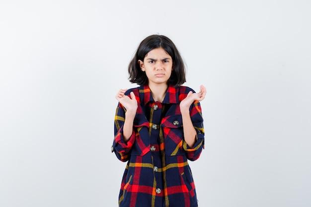 何かを持って、威嚇するように見えるように手を伸ばしてチェックシャツを着た少女、正面図。
