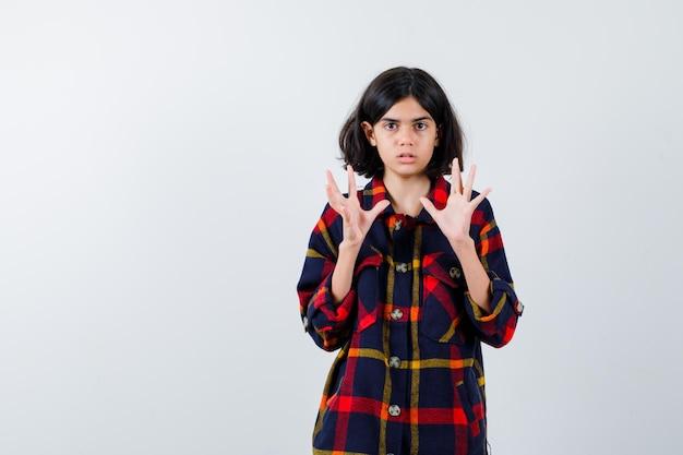 何かを持ってショックを受けたように手を伸ばしてチェックシャツを着た少女、正面図。