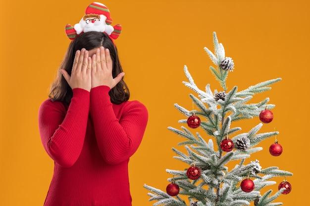 오렌지 배경 위에 크리스마스 트리 옆에 서있는 손으로 눈을 덮고 재미있는 머리띠를 쓰고 크리스마스 스웨터에 어린 소녀