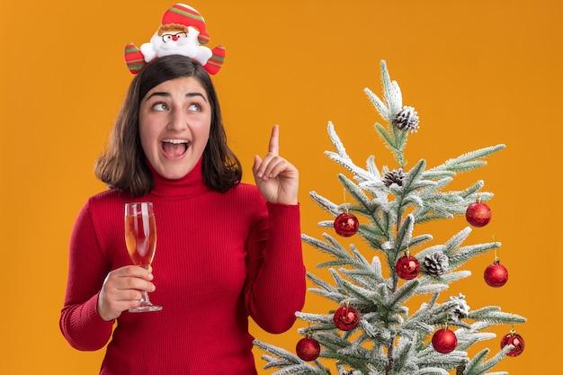 Молодая девушка в рождественском свитере с забавной повязкой на голову держит бокал шампанского, счастливая и удивленная, рядом с елкой на оранжевом фоне