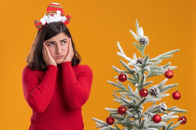 Молодая девушка в рождественском свитере с забавной повязкой на голову, смущенная и очень взволнованная, смотрит в сторону рядом с елкой на оранжевом фоне