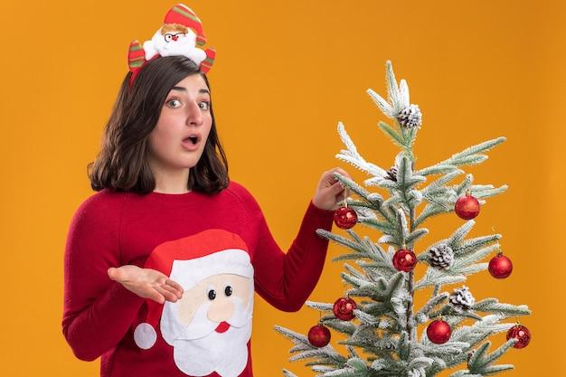 오렌지 배경 위에 크리스마스 트리 옆에 서 혼란 스 러 워 카메라를보고 재미있는 머리 띠를 입고 크리스마스 스웨터에 어린 소녀
