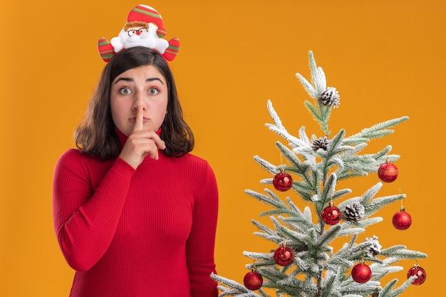 오렌지 배경 위에 크리스마스 트리 옆에 침묵 제스처를 만드는 카메라를보고 재미있는 머리띠를 입고 크리스마스 스웨터에 어린 소녀