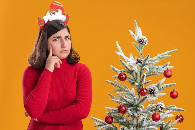 Молодая девушка в рождественском свитере с забавной повязкой на голову смотрит в камеру рядом с елкой на оранжевом фоне