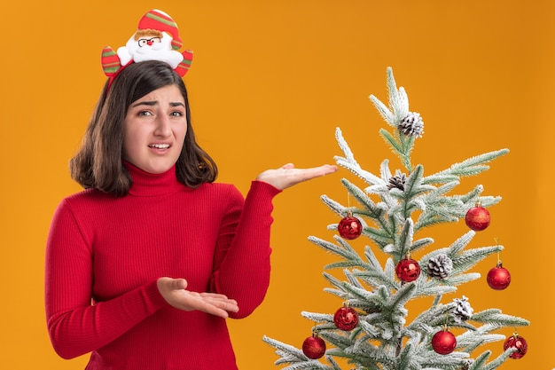 オレンジ色の背景の上のクリスマスツリーの横に面白いヘッドバンドを身に着けているクリスマスセーターの若い女の子