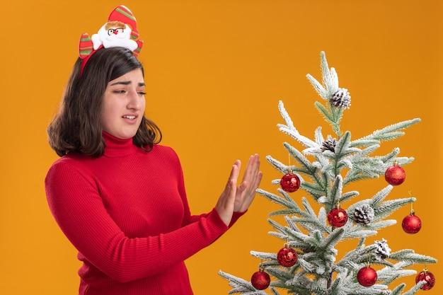 오렌지 배경 위에 크리스마스 트리 옆에 재미있는 머리띠를 입고 크리스마스 스웨터에 어린 소녀