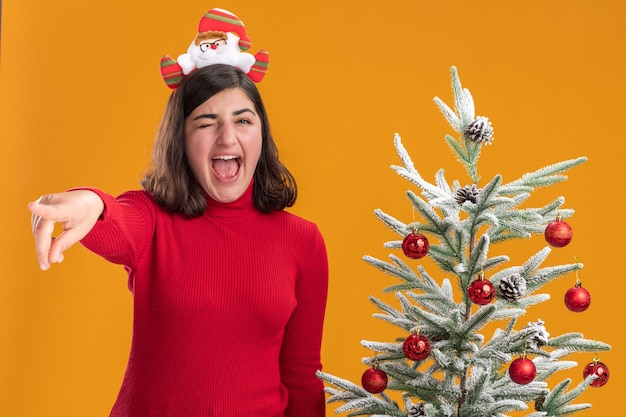 Молодая девушка в рождественском свитере с забавной повязкой на голове кричит рядом с елкой на оранжевом фоне